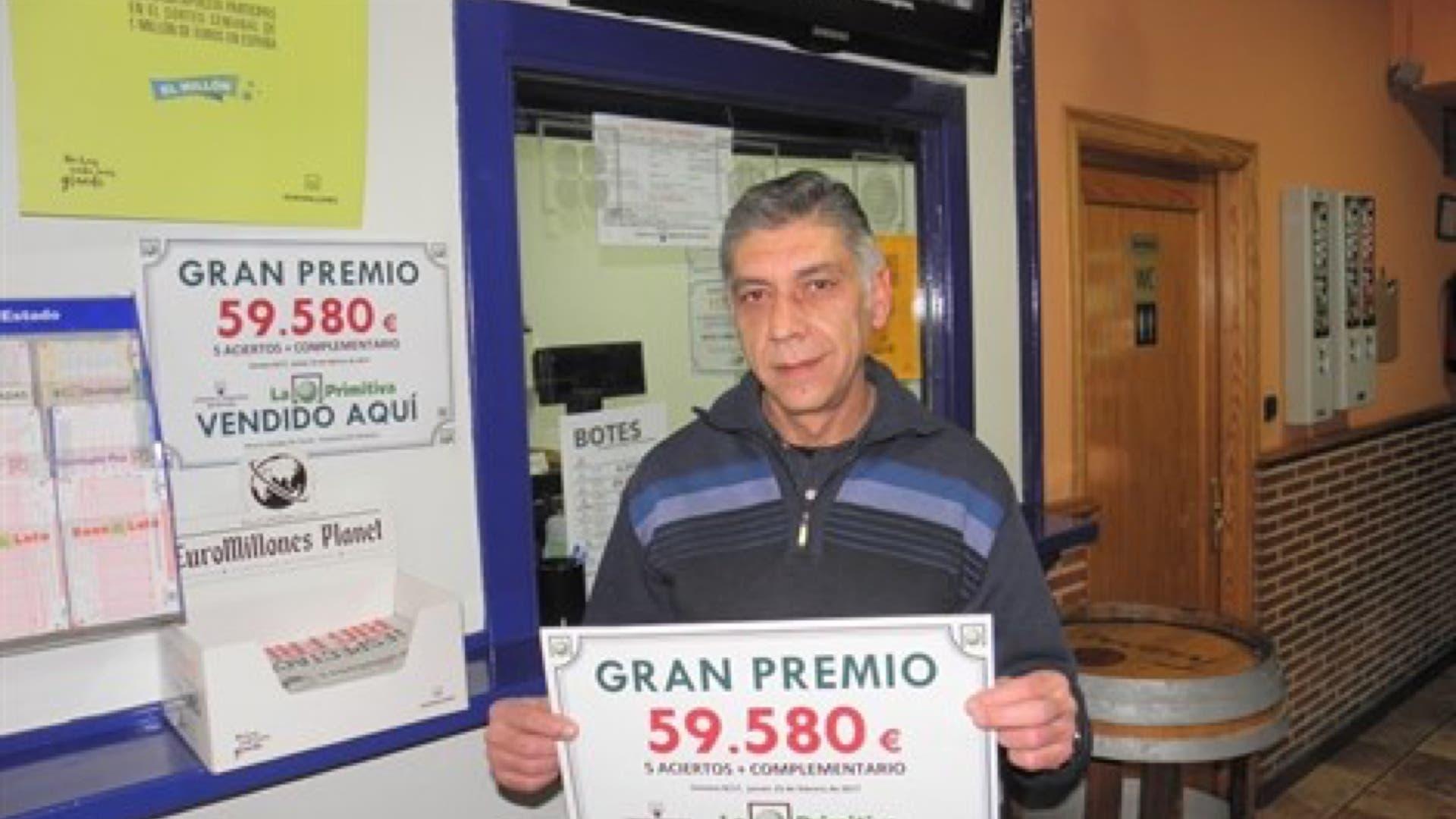 El propietario del bar con el cartel del premio (Loterías).