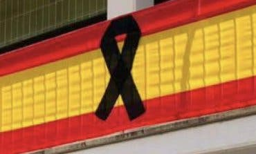 Meco coloca una gran bandera con crespones por las víctimas del coronavirus