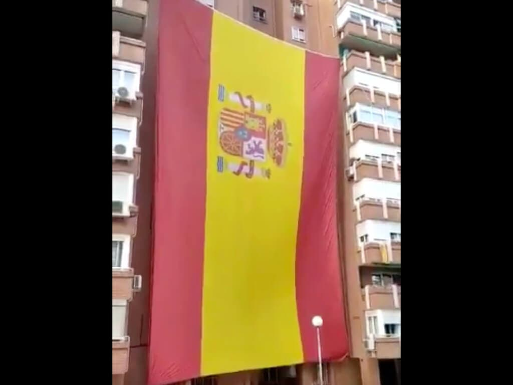 Vecinos del barrio del Pilar, en Madrid, despliegan una enorme bandera de España